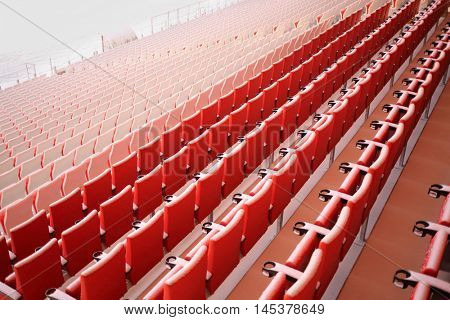 Red seats of grandstands covered by snow in modern stadium at winter