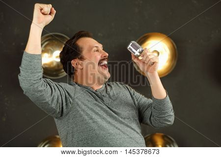 Smiling man with mustache sings with microphone in studio with lamps on wall