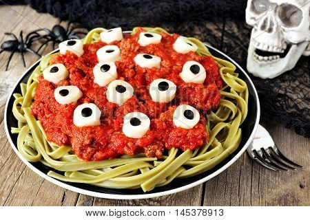 Halloween Cheesy Eyeball Pasta With Tomato Meat Sauce. Scene With Decor On Aged Wood.