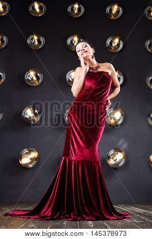 Happy girl poses in velvet long dress near wall with lamps in studio