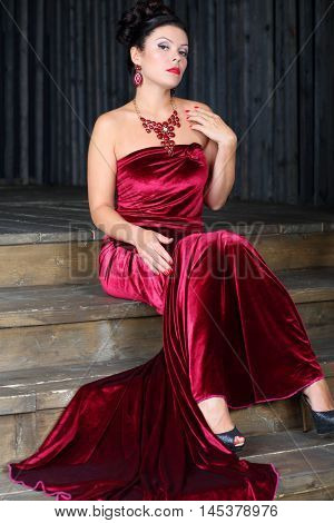 Pretty woman in red long velvet dress sits on stairs in studio