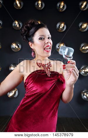 Pretty girl in red sings with microphone near wall with lamps