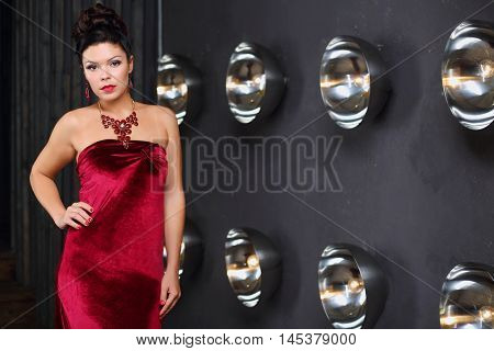 Pretty girl poses in red dress near wall with lamps in grey studio