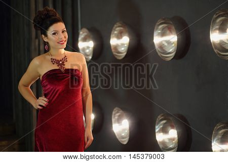 Smiling girl poses in red dress near wall with lamps in grey studio