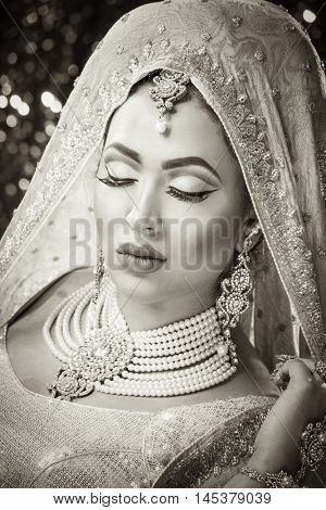 Pretty girl in traditional Indian Pakistani bridal costume with heavy makeup and jewellery against a glittery background