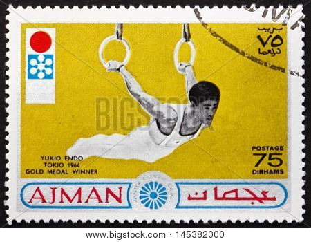 AJMAN - CIRCA 1964: a stamp printed in Ajman shows Yukio Endo Japanese Artistic Gymnast Tokio 1964 Gold Medal Winner circa 1964