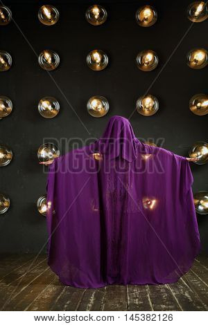 Woman in purple mantle poses near wall with lamps in studio, back view