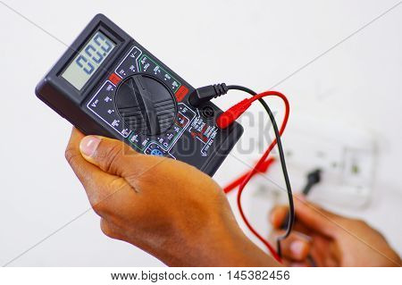 Closeup hands holding multimeter with wires connected and numbers showing on display.