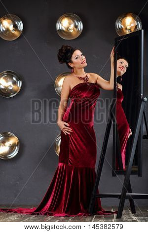 Brunette woman in red poses near mirror in studio with lamps on wall