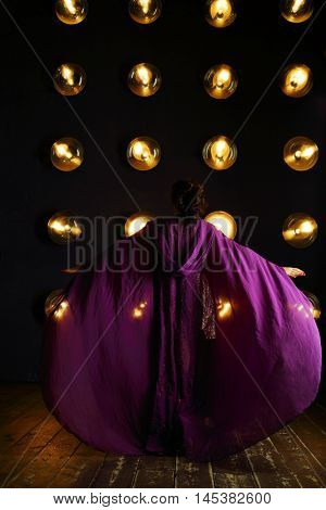 Girl in purple mantle poses near wall with lamps in studio, back view