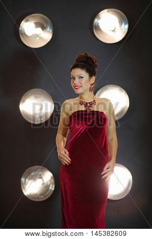 Beautiful smiling girl poses in red dress near wall with lamps in grey studio