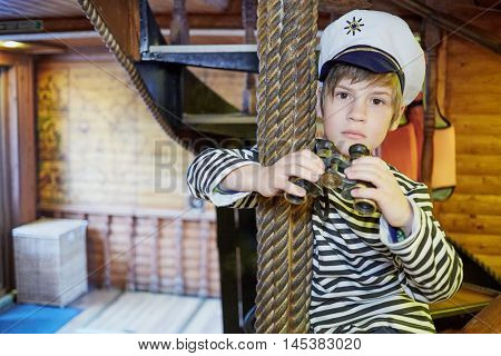Boy in striped vest and white cap with binoculars at room on pleasure boat.