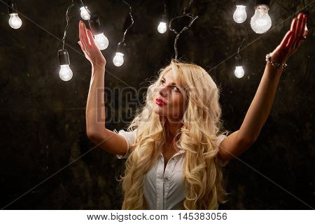 Young blonde woman stands raising her hands in dark room with many luminous lamps.