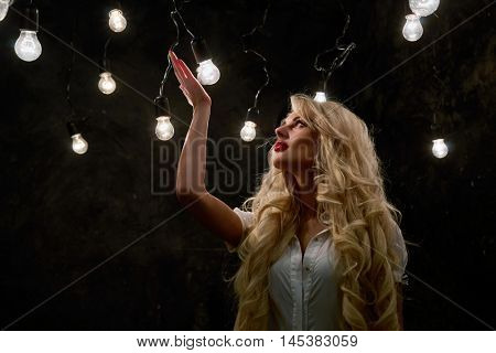 Young blonde woman stands in dark room with lots of luminous lamps.
