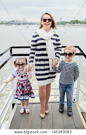 Mother and two children in dark sunglasses stand holding hands at pleasure boat stern.