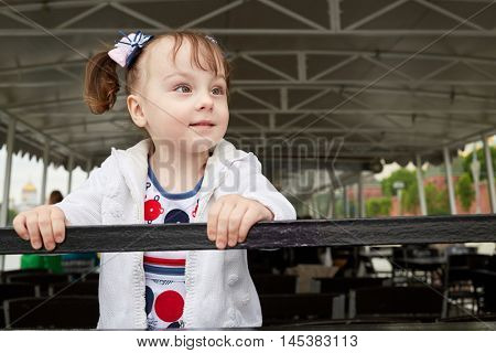 Little girl stands on pleasure boat stern, holding on railing.