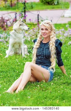Young blond woman sits on grassy lawn in park, dog sits behind her out of focus.