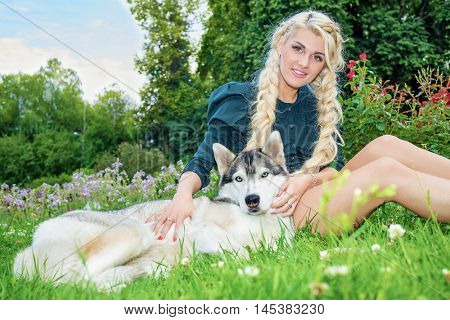 Young blond woman sits stroking husky dog on grassy lawn in summer park.
