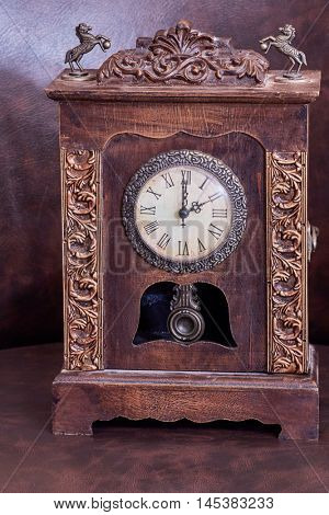 Old wooden clock with pendulum on leather armchair.