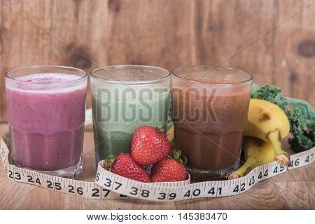 Three smoothie shakes in glasses on wood backgrounds with measuring tape laying in front