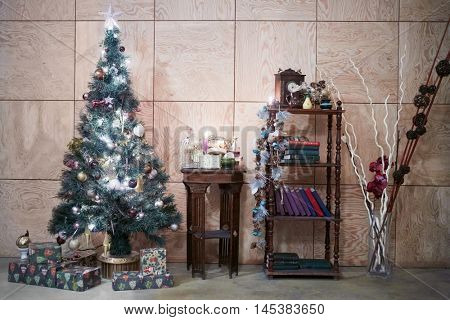 Room decorated to christmas holidays with artificial pine-tree and gift boxes.