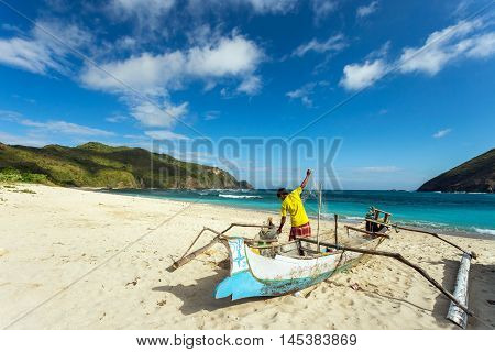 LOMBOK, INDONESIA - AUGUST 11, 2016: A fisherman works to untangle his net at Mawun beach in Southern Lombok.