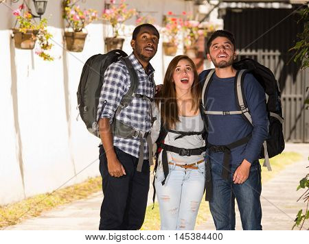 Two men standing with woman in middle, all wearing casual clothing and backpacks, staring up in awe of something, backpacker concept.