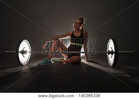 One woman on the floor with barbel. Concept of woman and fitness. Shallow depth of field. Low key.