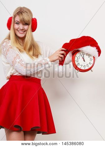 Happy cute woman holding alarm clock with santa claus hat. Pretty girl in earmuffs on gray. Christmas time season concept.