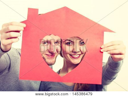 Young Cheerful Couple Holding House.