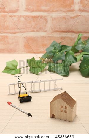House, ladder, high branch pruning shears, and lawn mower.  Miniature house and mowing equipment.