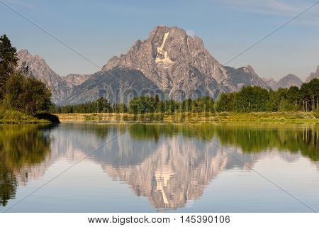 Beautiful Grand Teton mountain flecting on a smooth water surface with moonset behind the rock mountain. Oxbow Bend famous scenic point in Grand Teton National Park Wyoming USA.