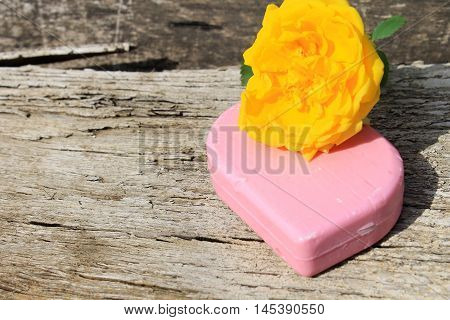 Soap and rose on the wooden background