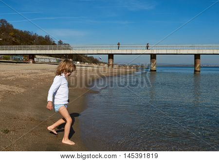 boy on the beach. he tries to water in the sea. Bulgaria Burgas