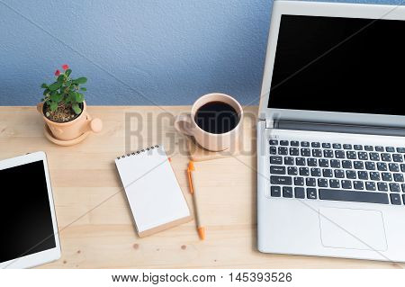 Office desk with blank screen laptop Note paper Euphorbia milii flower on terracotta flower pot and blank screen tablet. View from above wood table.