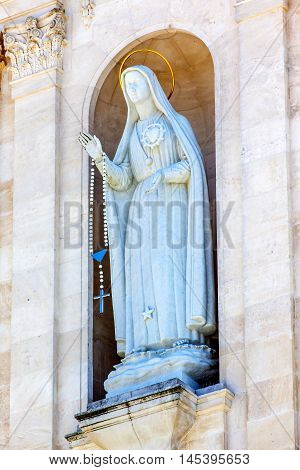 Mary RosFATIMA, PORTUGAL - MAY 11, 2014 ary Statue Bell Tower Basilica of Lady of Rosary Stone Fatima Portugal. Church created on site where three Portuguese Shepherd children saw Virgin Mary of the Rosary. Basilica created in 1953.