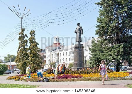 BELGOROD RUSSIA - August 30.2016: Brigade of workers engage in planting trees and shrubs of municipal service work on a flowerbed next to a monument to general Apanasenko