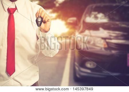 Male Holding Car Keys With Car On Background.vintage Color