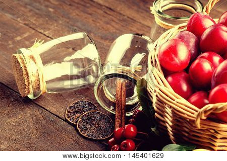 Plums in a basket, rowanberry and glass jars