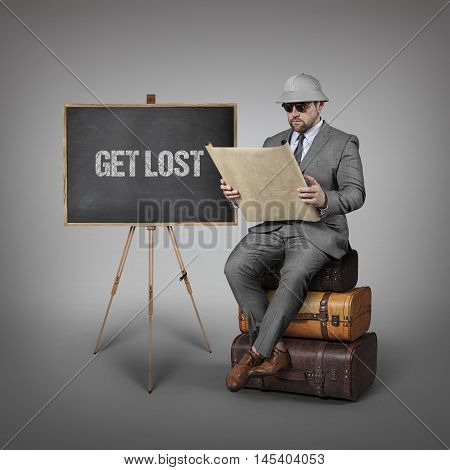 Get Lost text on  blackboard with explorer businessman sitting on suitcases