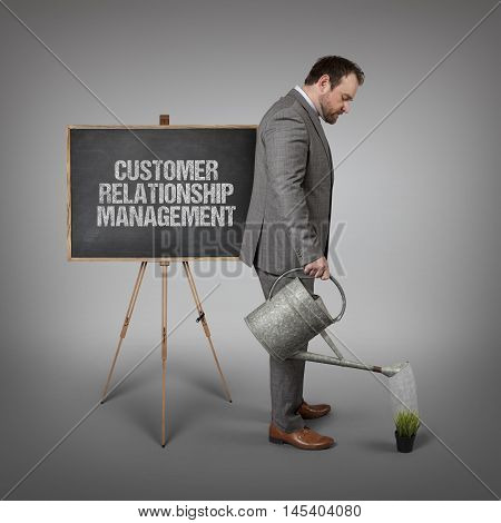 Customer relationship management text on  blackboard with businessman watering plant