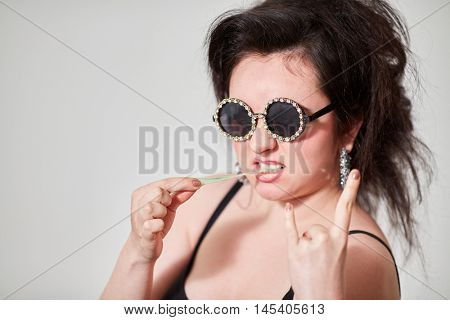 Dark-haired girl model in stylish round dark glasses shows goat and pulls chewing gum.