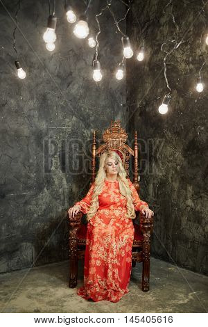 Woman in red dress sits on chair in room with luminous lamps hanging on wires from ceiling.