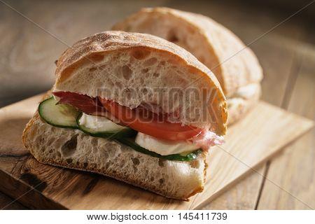 italian ciabatta sandwich with speck and mozzarella, closeup food photo