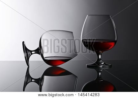 Two Snifters Of Brandy On Glass Table