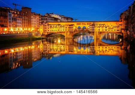 famous bridge Ponte Vecchio over river Arno at night, Florence, Italy, retro toned