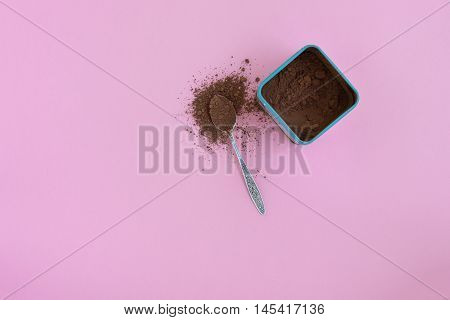Teaspoon with cocoa powder and box of cocoa over pink background, top view