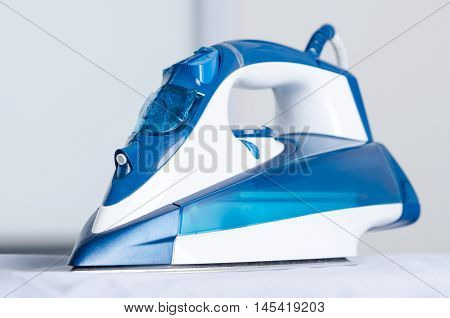 Modern Blue Steam Iron On Ironing Board
