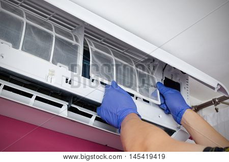 Air Conditioner Cleaning. Man Checks The Filter.