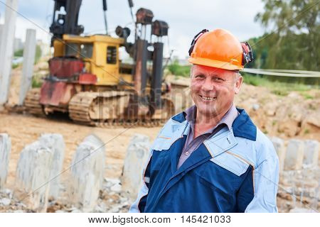 construction worker in front of pile driver machine